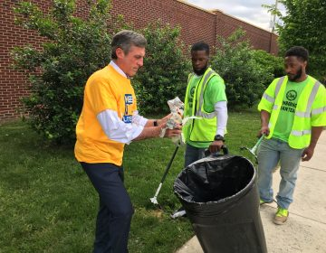 Gov. John Carney picks up litter along Vandever Ave. in northeast Wilmington. (Mark Eichmann/WHYY)