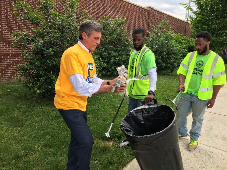 Gov. John Carney picks up litter along Vandever Ave. in northeast Wilmington. (Mark Eichmann/WHYY)