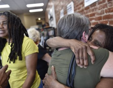 Janet Africa (right) embraces Betsy Piet while on the left, Janine Africa greets a well wisher. Janet and Janine Africa were recently released after serving 40 years in prison for their role in the shooting death of a police officer. (Jonathan Wilson for WHYY)
