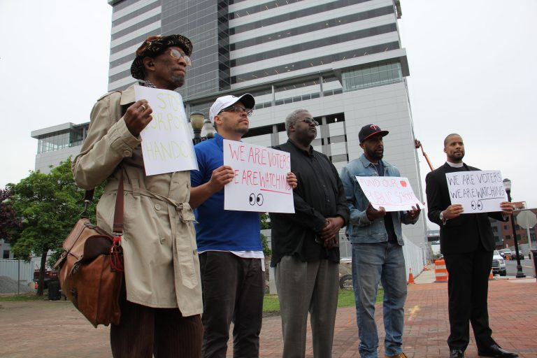 A small group of protesters gather outside Camden's newest corporate high rise, demanding that beneficiaries of state tax breaks demonstrate what they're doing to help Camden residents. (Emma Lee/WHYY)