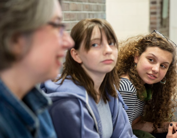 Sasha Mannino (center) and Iris Peron-Ames (right), both 15, look on as Kathryn Gay speaks with them Greenfield Elementary School on Tuesday. Graduates of Greenfield, Mannino and Peron-Ames now attend Science Leadership Academy and are running their second campaign to collect tampons and other toiletries for young people in need. (Heather Khalifa/The Philadelphia Inquirer)
