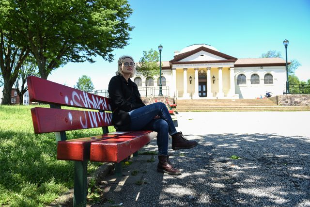 Chera Kowalski sits on a bench outside of McPherson Square Library on April 27, 2019. In 2017, when Kowalski was working as a librarian at McPherson, she convinced the Free Library of Philadelphia to offer overdose reversal training to employees. (Erin Blewett/Kensington Voice)