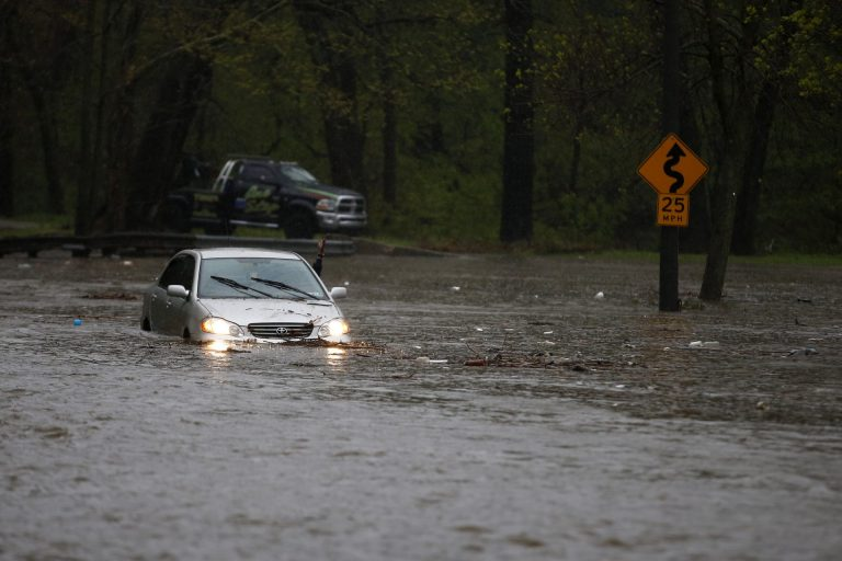 A man waves for a tow truck after getting swamped trying to cross a flooded section of the Cobbs Creek Parkway, Wednesday, April 30, 2014, in Philadelphia. Cobbs Creek and Darby Creek merge in the Eastwick section of Philadelphia where flooding is expected to get worse due to rising sea levels. (AP Photo)