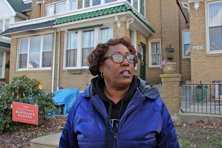 Tracey Gordon stands in front of homes in her Southwest Philadelphia neighborhood. (Emma Lee/WHYY)