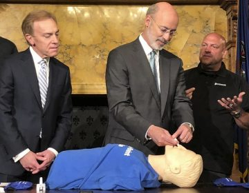 Gov. Tom Wolf listens to trainer Elvis Rosado, (right), of Philadelphia-based Prevention Point on how to administer a nasal spray that reverses an opioid overdose during a demonstration in Wolf's Capitol offices, Wednesday, May 22, 2019, in Harrisburg, Pa. Looking on is Paul Tufano, CEO of AmeriHealth Caritas, a Medicaid insurer that sponsors training. (Marc Levy/AP Photo)
