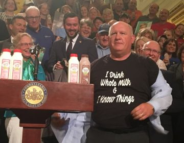 GOP Congressman Glenn Thompson displays his pro-dairy t-shirt to a surprised but appreciative crowd. (Katie Meyer/WITF)