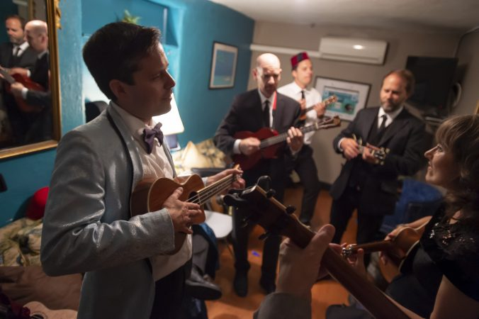 Members of the Philadelphia Ukulele Orchestra rehearse in their dressing room during intermission. (Jonathan Wilson for WHYY)