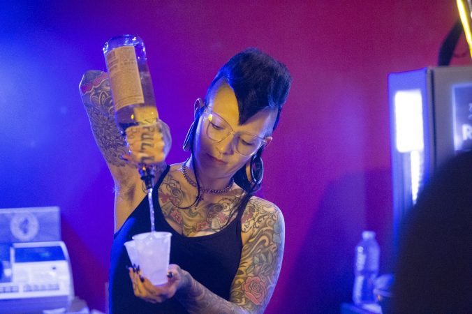 Luna Dahlia mixes drinks behind the bar prior to the last performance at the Troc. (Jonathan Wilson for WHYY)