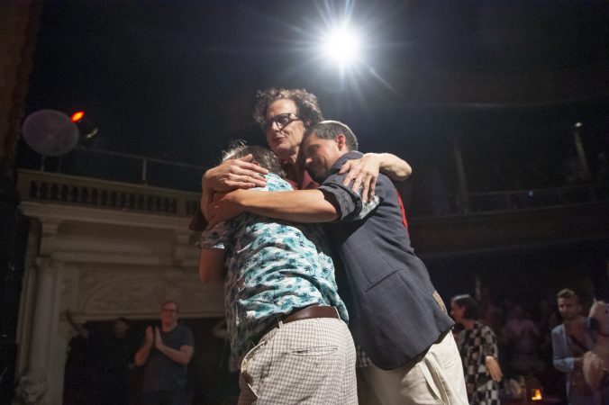 (From left) Greg Giovanni, Jimmy Mooney, and Sam Fulginiti embrace after the show. (Jonathan Wilson for WHYY)