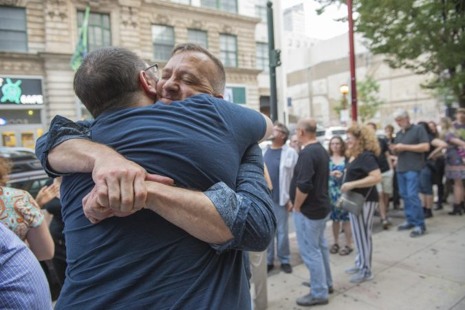 Big Mess Cabaret aficionados Pen Audley (left) and Everett Wilde greet each other in line while waiting for the final performance at the Troc. (Jonathan Wilson for WHYY)