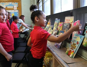 Angelis Leon, a third grader at Gilbert Spruance Elementary School, finds the books she ordered through the Book Trust. The non-profit allows young readers to choose their books.