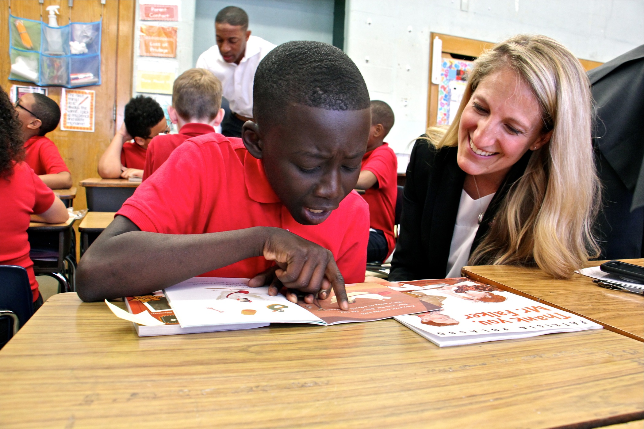 Harley Belance, 9, a thrid grader at Gilbert Spruance Elementary School, reads with Tiffany Kuehner, president and CEO of the Book Trust.