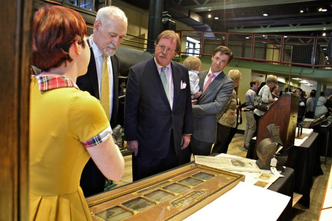 Members of the Hamilton family listen as curatorial assistant Ariel McManus (left) describes items in the Franklin Institute's collection which will be displayed in the new space. (Emma Lee/WHYY)