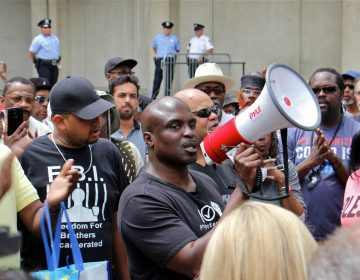 Columnist and commentator Solomon Jones leads a rally at Philadelphia police headquarters to call for action against police officers who posted racist comments on Facebook. (Emma Lee/WHYY)