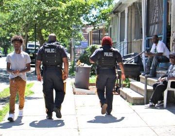 Trenton police officers patrol on foot on Walnut Street, where one person was killed and five injured in a mass shooting on May 28. (Emma Lee/WHYY)