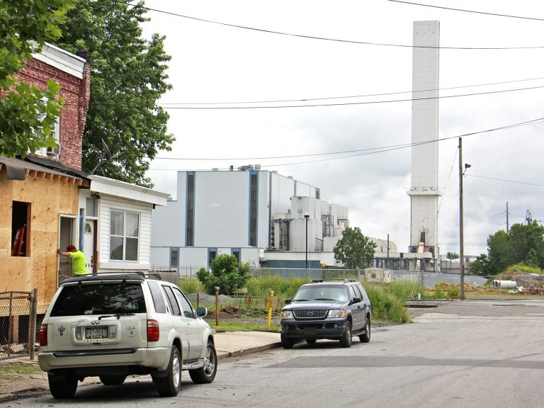 The smokestack of the Delaware Valley Resource Recovery Facility looms over a residential street in Chester. (Emma Lee/WHYY)