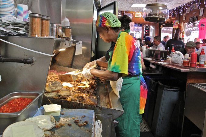 A fry cook tends to meat and onions sizzling on the griddle at Donkey's Place in Camden. (Emma Lee/WHYY)