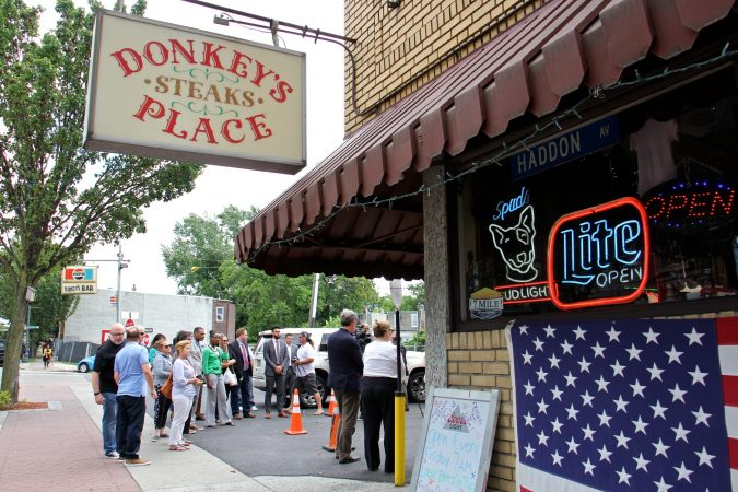 A small crowd gathers outside Donkey's Place in Camden for the announcement of the Anthony Bourdain Food Trail. (Emma Lee/WHYY)