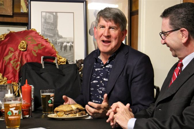 Anthony Bourdain's brother, Chris, sits down to a Donkey's cheesesteak with N.J. Assemblyman Paul Moriarity, who sponsored the resolution establishing the Anthony Bourdain Food Trail. (Emma Lee/WHYY)