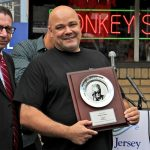 Rob Lucas, owner of Donkey's Place in Camden, holds a plaque that recognizes his restaurant's inclusion in the Anthony Bourdain Food Trail, which identifies ten New Jersey restaurants visited by the celebrity chef. (Emma Lee/WHYY)