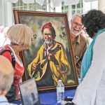 An appraiser examines a painting at the Antiques Roadshow taping at Winerthur. (Kimberly Paynter/WHYY)