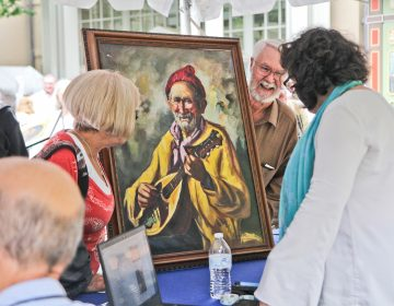 An appraiser examines a painting at the Antiques Roadshow taping at Winterthur. (Kimberly Paynter/WHYY)
