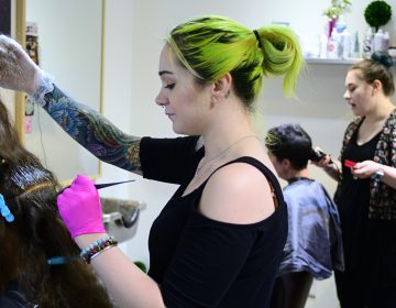 Kristina Amell and Grace Berry attend to clients at Starshine Salon, located on Manayunk's Main Street. (Bastiaan Slabbers for WHYY)