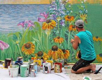 Philadelphia artist Charles Barbin covers a cinderblock wall with a seascape mural at the home of Rose Ann Cahill in Ventnor. The bayside home was raised 8 feet after it was damaged by Superstorm Sandy. (Emma Lee/WHYY)