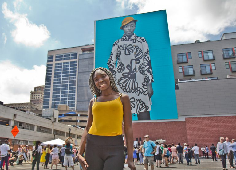 Najee Spencer-Young poses in front of her mural portrait by artist Amy Sherald. Spencer-Young is a participant in the Mural Arts' Achieving Independence Center classes. (Kimberly Paynter/WHYY)