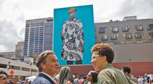 Realist painter Bo Bartlett talks with artist Amy Sherald (right) at the dedication of Sherald's mural portrait of young Philadelphian, Najee Spencer-Young. (Kimberly Paynter/WHYY)
