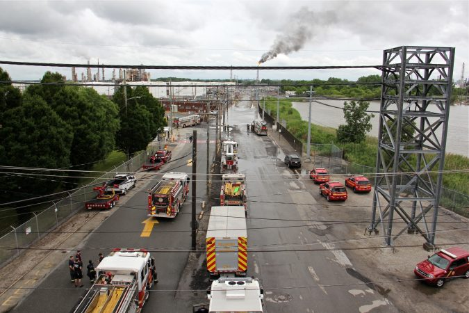 In this file photo, Philadelphia firefighters gather at the entrance to Philadelphia Energy Solutions Refinery, while a large flare burns off fuel to prevent it from feeding the massive fire at the refinery, Friday, June 21, 2019. (Emma Lee/WHYY, file)