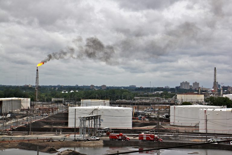 A large flare burns off fuel at Philadelphia Energy Solutions refinery while firefighters battle a fire there. The wind carried the black smoke toward residential areas of South Philadelphia. (Emma lee/WHYY)