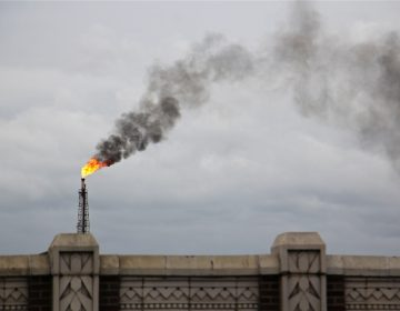 A large flare burns off fuel at Philadelphia Energy Solutions refinery while firefighters battle a fire there. (Emma lee/WHYY)