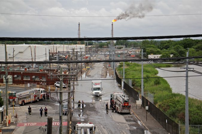 Philadelphia firefighters gather at the entrance to Philadelphia Energy Solutions Refinery, while a large flare burns off fuel to prevent it from feeding the massive fire at the refinery. (Emma Lee/WHYY)
