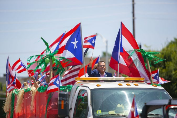 Camden City Councilman Angel Fuentes greets the crowd at the San Juan Bautista Parade and Festival. (Miguel Martinez/WHYY)