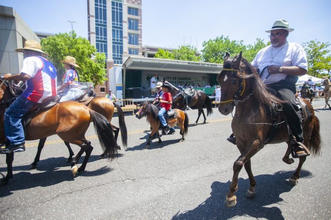 Horse riders parade through the streets of Camden during the San Juan Bautista Parade and Festival. (Miguel Martinez/WHYY)