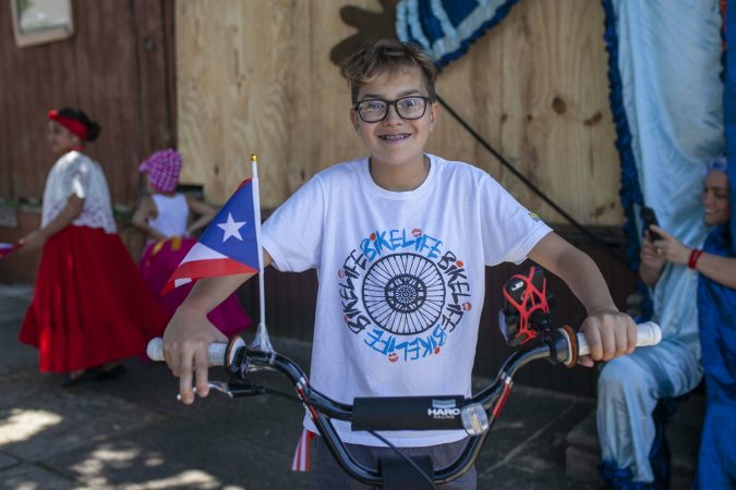 Angel  Soldevilla, 13, from Camden rides his decorated bike to celebrate the San Juan Bautista Parade and Festival. (Miguel Martinez/WHYY)