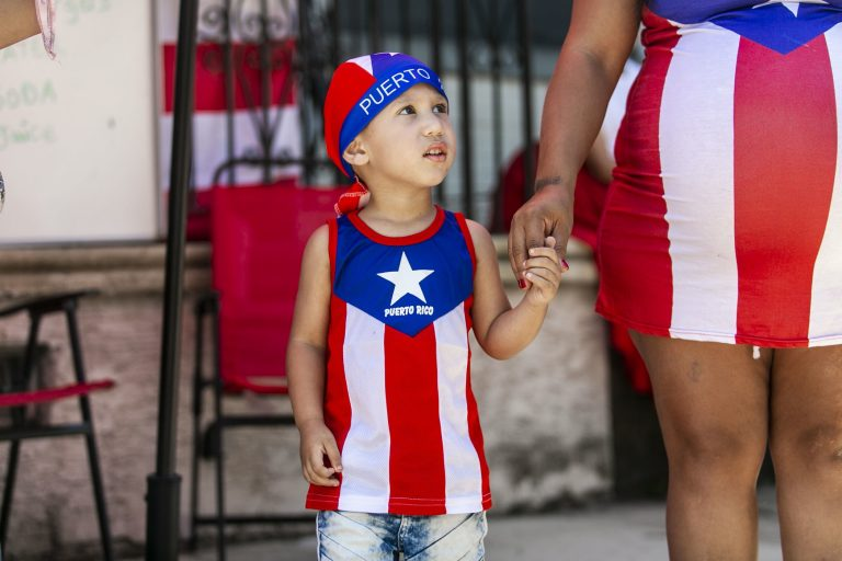 Jashua Vargas from Camden takes part in the San Juan Bautista Parade and Festival on the Camden waterfront. The parade has been a tradition in the city for the 62 years. (Miguel Martinez/WHYY)