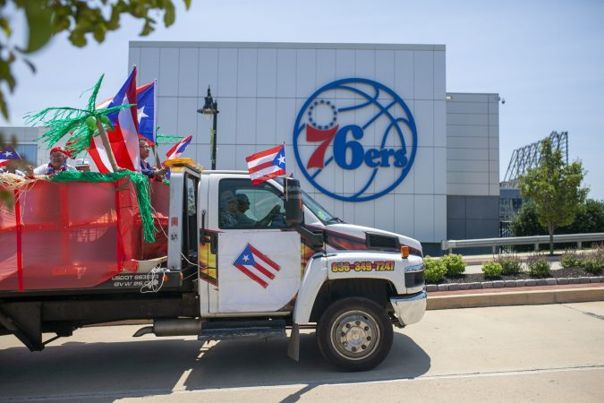A truck with Puerto Rican flags drives past the new 76ers building as part of the San Juan Bautista Parade and Festival. The parade has been a tradition in the city for the past 62 years. (Miguel Martinez/WHYY)