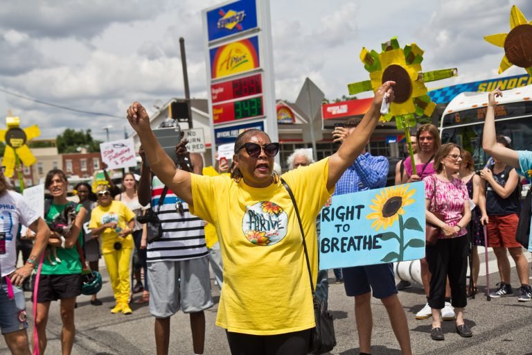 Sylvia Bennett, a member of Philly Thrive, raises her arms at a protest outside Philadelphia's PES refinery. (Kimberly Paynter/WHYY)