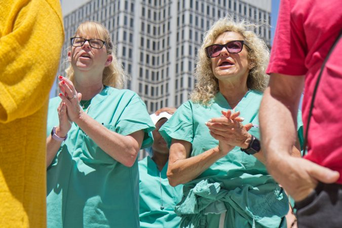Hahnemman OR nurses Michelle Guth (left) and Judy Schneider (right) chant at a rally to save Hahnemman from closing at City Hall Thursday. (Kimberly Paynter/WHYY)