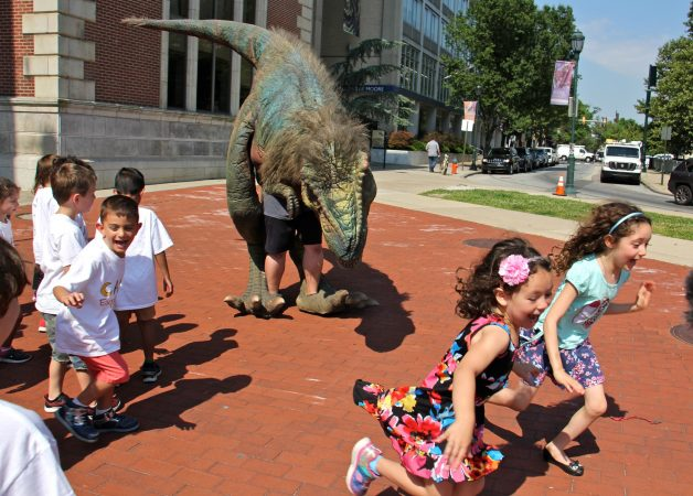 Children run shrieking from a man in a dinsaur costume outside the Academy of Natural Sciences. (Emma Lee/WHYY)