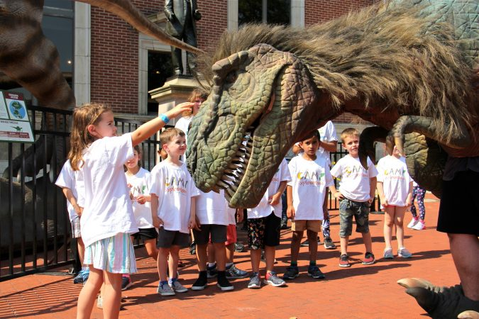 Chloe Herman, 5, reaches out to touch the head of a dinosaur costume worn by an employee of the Academy of Natural Sciences. (Emma Lee/WHYY)