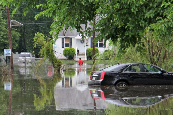 A man makes his way through waist-deep waters in a flooded area between High Street and Broadway in Westville, N.J. (Emma Lee/WHYY)