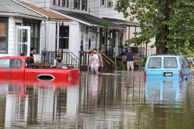 Residents of High Street in Westville, N.J., return to their homes as flood waters begin to recede. (Emma Lee/WHYY)