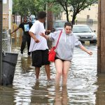 Westville residents (from right) Amberly Lynn, Jay Gray and Lamar Majette, wade through flood waters on Broadway. (Emma Lee/WHYY)