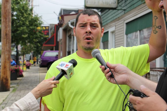 Brandon Myers talks to reporters about the flooding at his home on High Street in Westville, which forced him and his family to evacuate. (Emma Lee/WHYY)