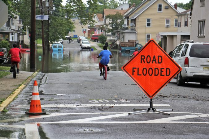 Children on bicycles check out the flooding on High Street in Westville, N.J. (Emma Lee/WHYY)