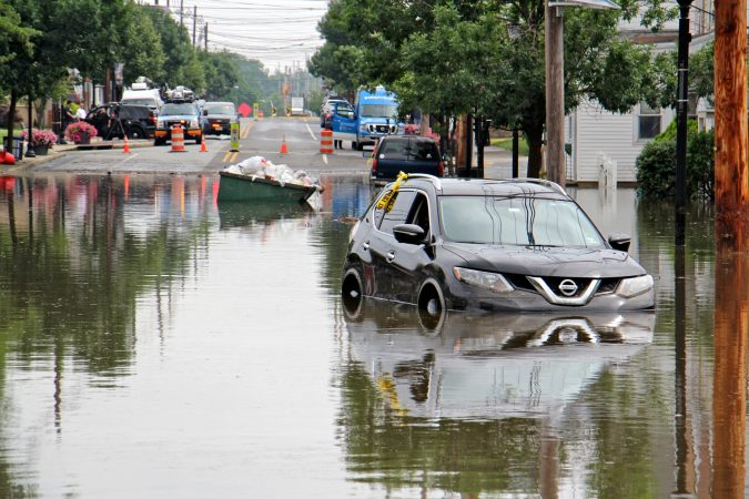 A dumpster floats among the abandoned cars on Broadway in Westville, N.J. (Emma Lee/WHYY)