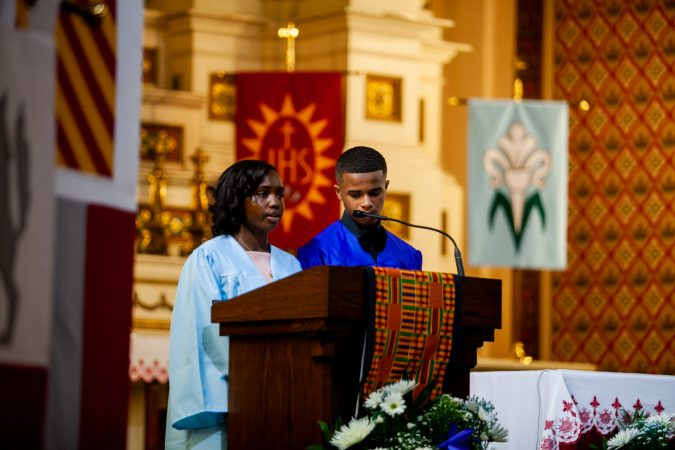 Graduating students of the Gesu School Nateerah Ransome and Alphonso Evans Jr. welcome students and parents to the school's graduation ceremony. (Brad Larrison for WHYY)